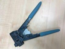 有蓝色把柄的钳子工具为起皱对网络的一个连接器 免版税库存图片