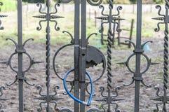 有蓝色挂锁的老生锈的篱芭 图库摄影
