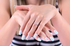 有蓝色指甲油修指甲和金刚石订婚婚戒的女孩手 免版税库存图片