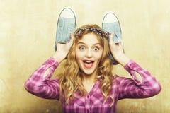 有蓝色时尚运动鞋的惊奇俏丽的女孩在手上 库存照片