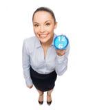 有蓝色时钟的微笑的女实业家 库存图片