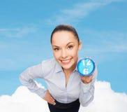 有蓝色时钟的微笑的女实业家 免版税库存图片