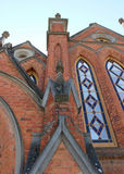 有蓝色污迹玻璃窗的红砖教会 图库摄影