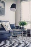 有蓝色沙发和圆桌的现代客厅在地毯 免版税库存图片