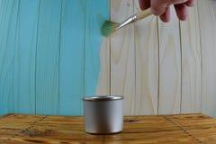 有蓝色油漆和刷子的瓶子在手中 图库摄影