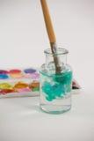 有蓝色油漆的油漆刷被浸洗入瓶子用水填装了 库存照片