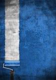有蓝色油漆的漆滚筒在空白墙壁上 免版税图库摄影