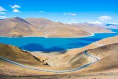 有蓝色湖和山的美丽的路 免版税库存照片