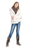 有蓝色牛仔裤、站立pos的冬天夹克和起动的女孩 免版税库存图片