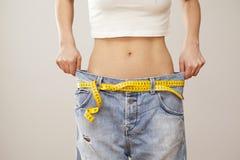 有蓝色牛仔裤的减重妇女 免版税库存图片