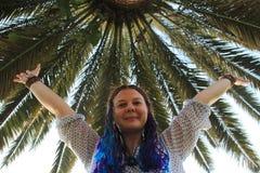 有蓝色猪尾微笑和波浪的白女孩她的在棕榈背景的手  库存图片