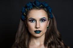 有蓝色玫瑰花圈的妇女  图库摄影