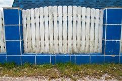 有蓝色瓦片的老白色篱芭 库存图片