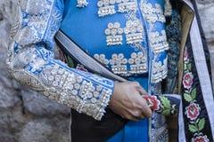 有蓝色礼服和银装饰品的西班牙斗牛士,披风安置开始paseíllo 图库摄影