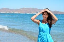有蓝色礼服的美丽的妇女在海背景 库存图片