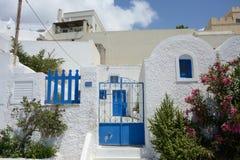 有蓝色窗口、蓝色门和一棵夹竹桃植物的典型的白色希腊房子有花的 库存图片