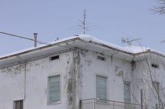 有蓝色窗口和多雪的屋顶的被破坏的老房子 免版税库存照片