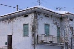 有蓝色窗口和多雪的屋顶的被破坏的老房子 库存照片