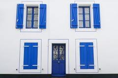 有蓝色窗口和快门,开放和闭合的快门的白色门面房子 库存照片