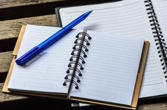 有蓝色笔的笔记本在木桌上 图库摄影