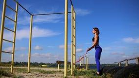 有蓝色绑腿的逗人喜爱的运动的浅黑肤色的男人执行锻炼加强手的肌肉在街道的与 影视素材