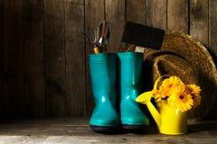 有蓝色胶靴的园艺工具,染黄春天花  免版税图库摄影