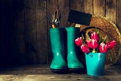 有蓝色胶靴的,草帽,春天花园艺工具 免版税库存图片