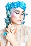 有蓝色花的女孩在蓝色头发。 图库摄影
