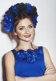 有蓝色花的美丽的女孩 图库摄影