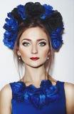 有蓝色花的美丽的女孩 免版税库存照片