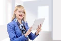 有蓝色衣服的美丽的现代女实业家,拿着片剂co 免版税库存照片