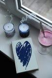 有蓝色设计心脏盖子的笔记本在窗台 吹灭与烟,在高玻璃觚的圆滑的人的蜡烛 图库摄影