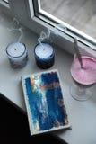 有蓝色设计盖子的笔记本在窗台 吹灭与烟,在高玻璃觚的圆滑的人饮料的蜡烛 库存照片
