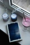 有蓝色设计盖子的笔记本在窗台 吹灭与烟,在高玻璃觚的圆滑的人饮料的蜡烛 库存图片