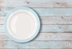 有蓝色边界的白色空的菜盘在木桌上 免版税库存照片