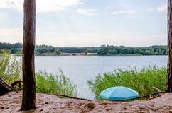 有蓝色遮阳伞的Summer湖 免版税库存照片
