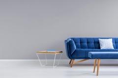 有蓝色长沙发的灰色室 免版税库存图片
