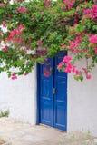 有蓝色门和桃红色九重葛的,希腊白宫 库存照片