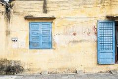 有蓝色门和窗口的土气墙壁。 库存照片