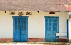 有蓝色门和窗口的老房子墙壁 免版税库存照片