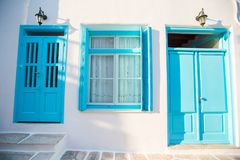 有蓝色门的传统房子在米科诺斯岛,希腊狭窄的街道  免版税库存照片