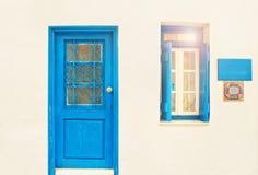 有蓝色门的白色房子和开窗口在晴天 库存图片