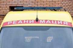 有蓝色闪光灯的救护车汽车在屋顶 在russ的文本 免版税库存照片