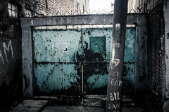 有蓝色颜色的一个被放弃的老和难看的东西门在雅加达拍的胡同照片印度尼西亚 免版税库存图片