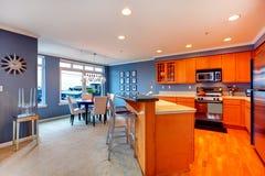 有蓝色餐厅的城市公寓橙色木厨房。 免版税库存图片