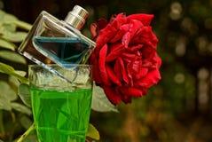 有蓝色香水的一个瓶在与一份饮料的一块玻璃在红色玫瑰附近 图库摄影