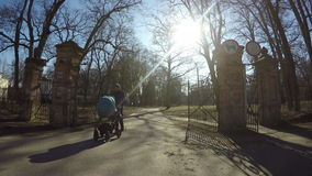 有蓝色婴儿推车步行减速火箭的公园门的父亲人在春天 4K 股票视频