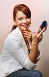 有蓝色紧凑镜子的愉快的妇女 图库摄影