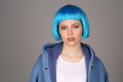 有蓝色头发和外套摆在的夫人 关闭 灰色背景 免版税库存图片