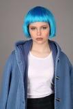 有蓝色头发和外套的女孩 关闭 灰色背景 库存照片